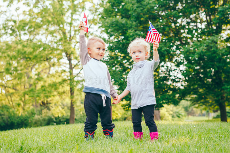 Riso de sorriso da menina e do menino guardando as mãos e acenando as bandeiras americanas e canadenses, parte externa no parque fotografia de stock