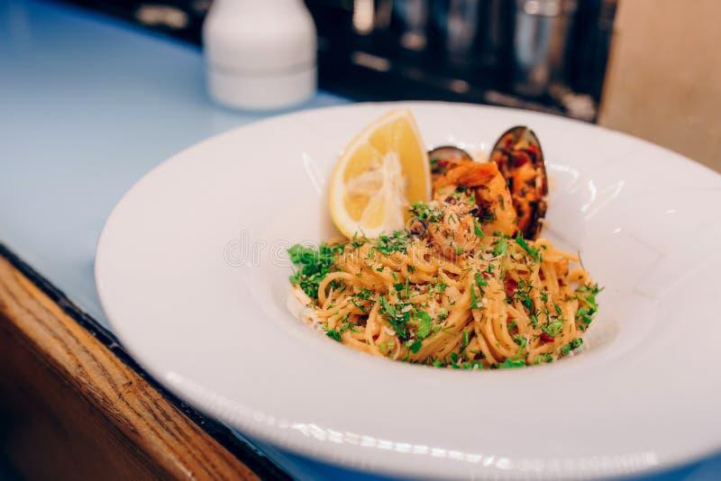Riso del nero degli spaghetti con frutti di mare nel sause con la fetta del limone spaghetti con l'inchiostro del calamaro delle  immagine stock libera da diritti