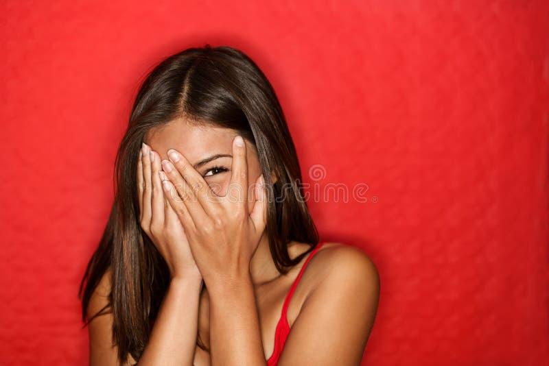 Riso escondendo da face da mulher tímida brincalhão imagem de stock royalty free