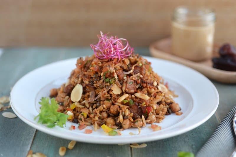 Riso fritto nello stile indonesiano con esperta carne di maiale e le arachidi sopra immagine stock libera da diritti