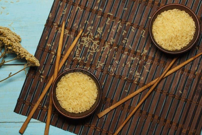 Riso giapponese in una ciotola di legno Bastoncini di legno sulla tavola di una stuoia di bambù Cucina asiatica Vista da sopra immagine stock