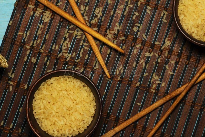 Riso giapponese in una ciotola di legno Bastoncini di legno sulla tavola di una stuoia di bambù Cucina asiatica Vista da sopra fotografia stock libera da diritti