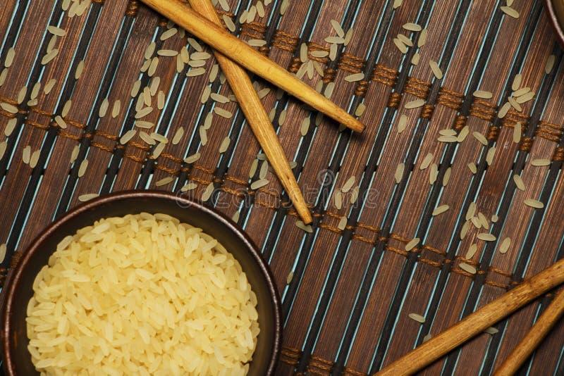 Riso giapponese in una ciotola di legno Bastoncini di legno sulla tavola di una stuoia di bambù Cucina asiatica Vista da sopra fotografia stock
