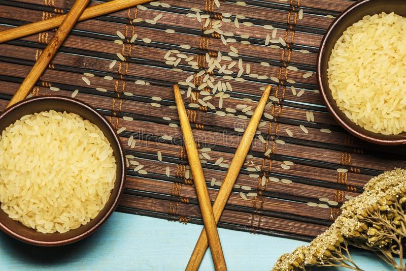 Riso giapponese in una ciotola di legno Bastoncini di legno sulla tavola di una stuoia di bambù Cucina asiatica Vista da sopra immagine stock libera da diritti