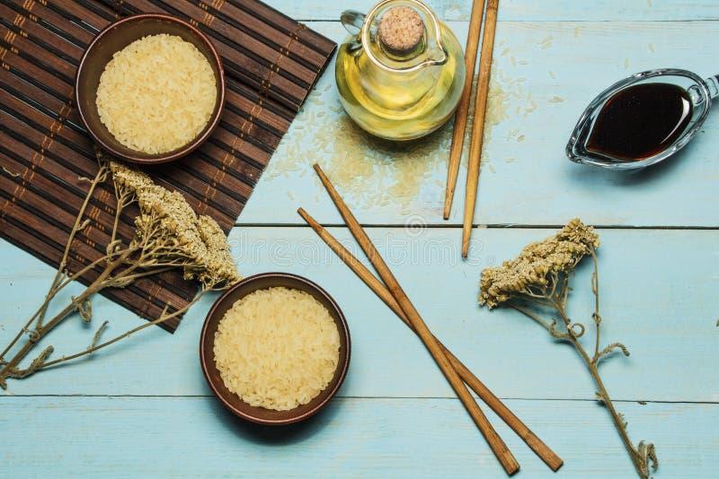Riso giapponese in una ciotola di legno Bastoncini di legno sulla tavola di una stuoia di bambù Cucina asiatica Vista da sopra immagini stock libere da diritti