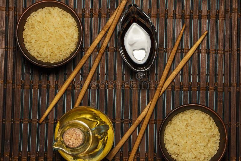 Riso giapponese in una ciotola di legno Bastoncini di legno sulla tavola di una stuoia di bambù Cucina asiatica Vista da sopra fotografie stock