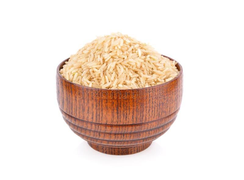 Riso marrone organico crudo del gelsomino in ciotola di legno su fondo bianco fotografia stock