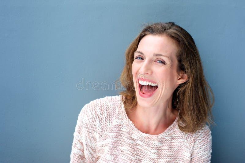 Riso meados de fresco bonito feliz da mulher adulta fotografia de stock