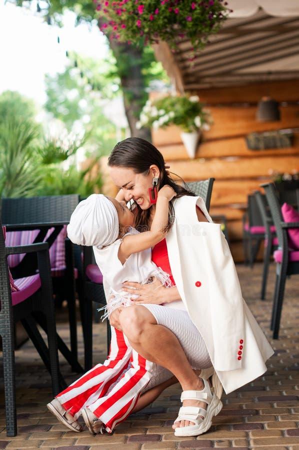 Riso na moda da mamã e da filha que abraça-se imagem de stock