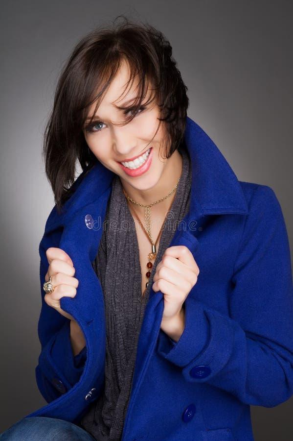 Riso novo e seguro bonito da mulher Obscuridade vestindo - revestimento azul do inverno Retrato do estúdio foto de stock royalty free
