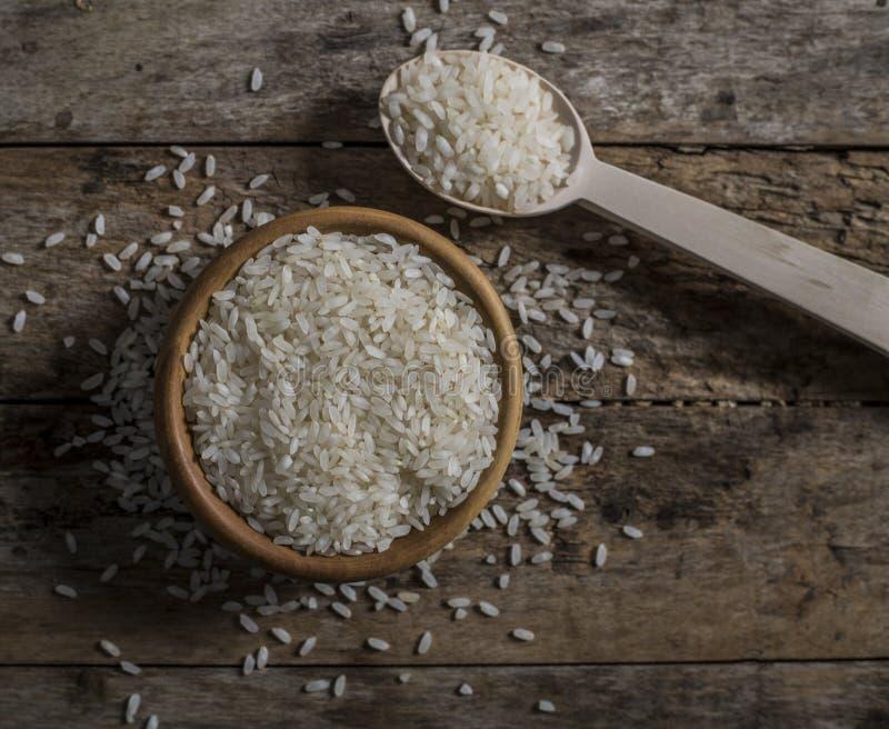 Riso, riso del gelsomino, riso del Mali in siviera e canestro sui precedenti di legno fotografia stock