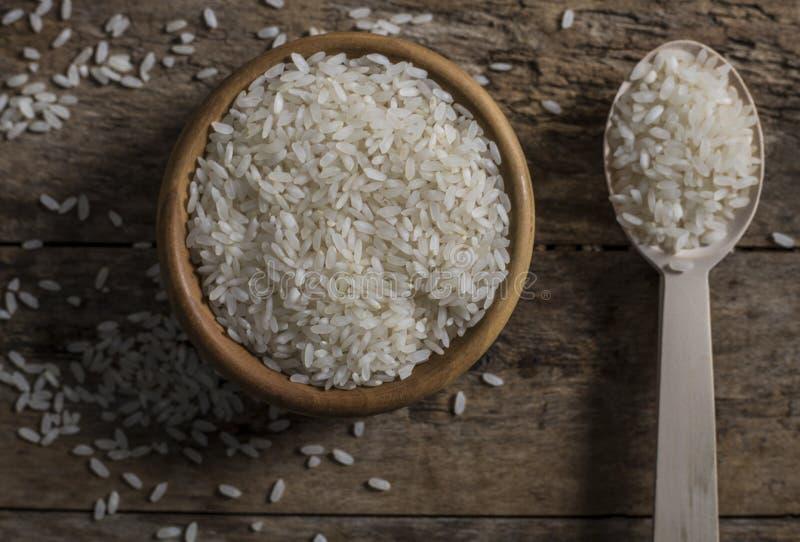 Riso, riso del gelsomino, riso del Mali in siviera e canestro sui precedenti di legno immagine stock libera da diritti