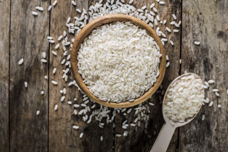 Riso, riso del gelsomino, riso del Mali in siviera e canestro sui precedenti di legno fotografia stock libera da diritti