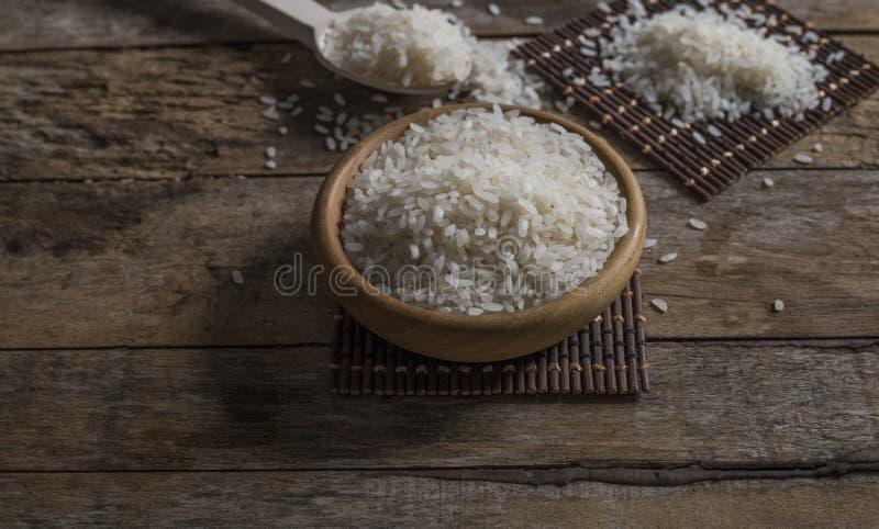 Riso, riso del gelsomino, riso del Mali in siviera e canestro sui precedenti di legno immagini stock