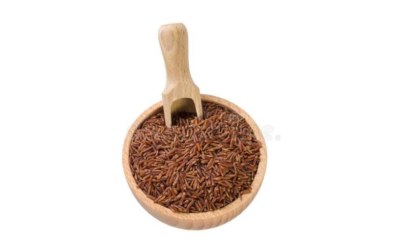 Riso rosso in ciotola di legno e mestolo isolati su fondo bianco nutrizione bio- Ingrediente di alimento naturale immagine stock