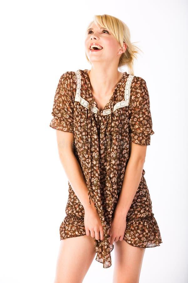Riso surpreendido louro no mini vestido fotografia de stock
