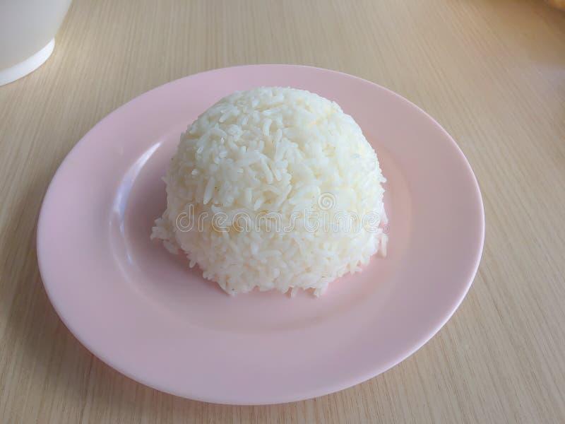 Riso tailandese del gelsomino cucinato in un piatto su una tavola di legno fotografie stock libere da diritti