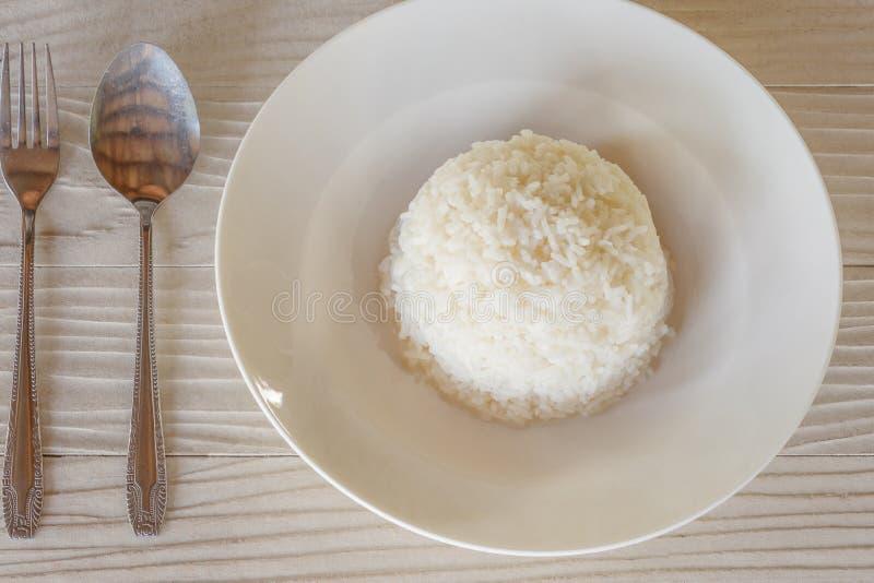 Riso in una forchetta ed in un cucchiaio del piatto fotografia stock