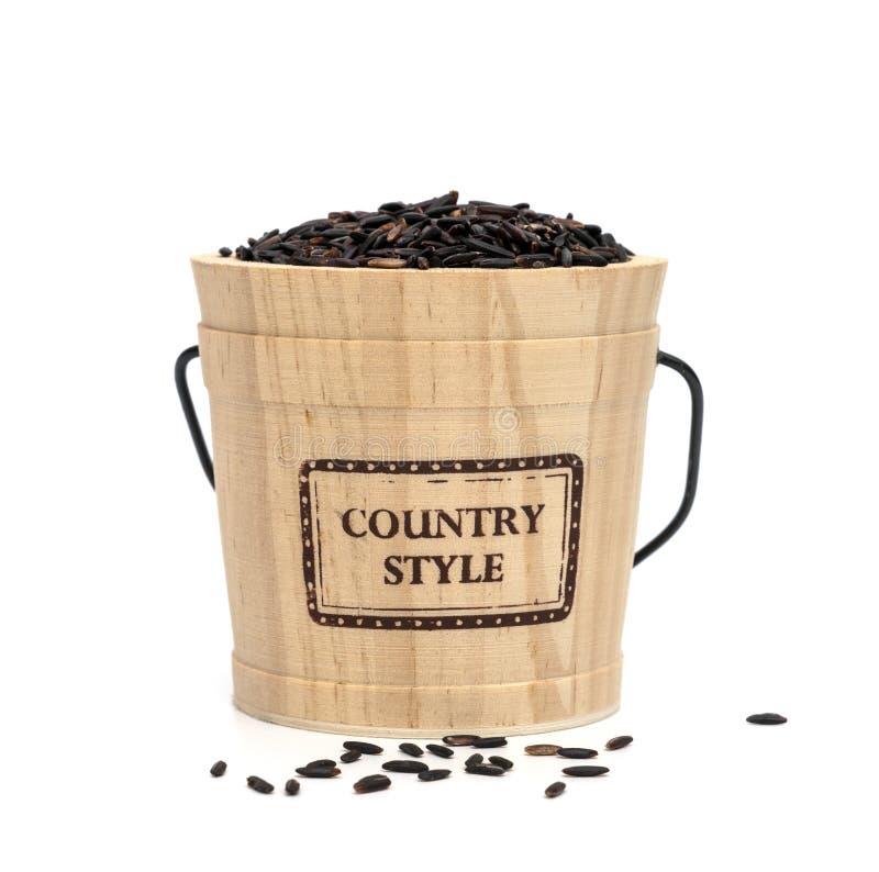 Riso viola scuro della bacca imballato in secchio di legno, isolato su fondo bianco fotografia stock libera da diritti