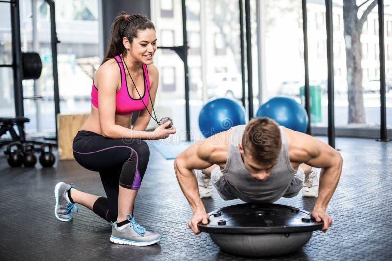 Risolvere atletico dell'uomo aiutato dalla donna dell'istruttore immagine stock