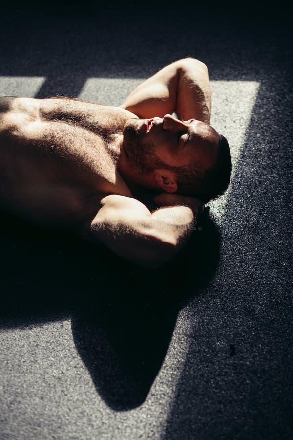 Risolvere maschio di forma fisica alla palestra Giovane muscolare che fa gli esercizi di stomaco immagini stock libere da diritti