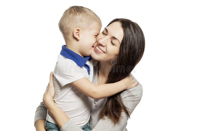 Risos bonitos e abraços do rapaz pequeno com a mamã, isolada no fundo branco Ternura e amor imagem de stock royalty free