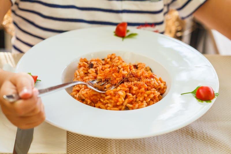 Risoto com molho do marisco e de tomate na placa branca na tabela no restaurante fotografia de stock