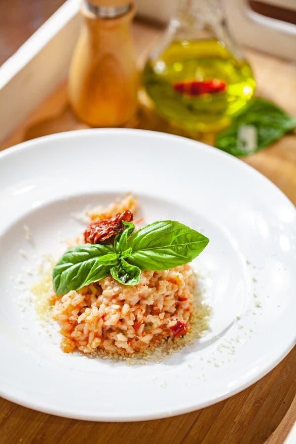 Risoto com tomates e as alcaparras sol-secados na placa branca fotos de stock royalty free