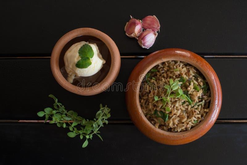 Risoto do arroz integral com folhas dos oréganos e sobremesa do gelado do limão com as folhas da manjericão na placa cerâmica sob foto de stock