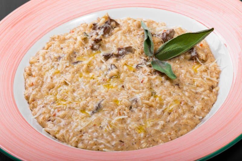 Risotto με το συκώτι κοτόπουλου, το τυρί παρμεζάνας, το έλαιο και τη φασκομηλιά στο πιάτο στο μαύρο ξύλινο υπόβαθρο στοκ εικόνες