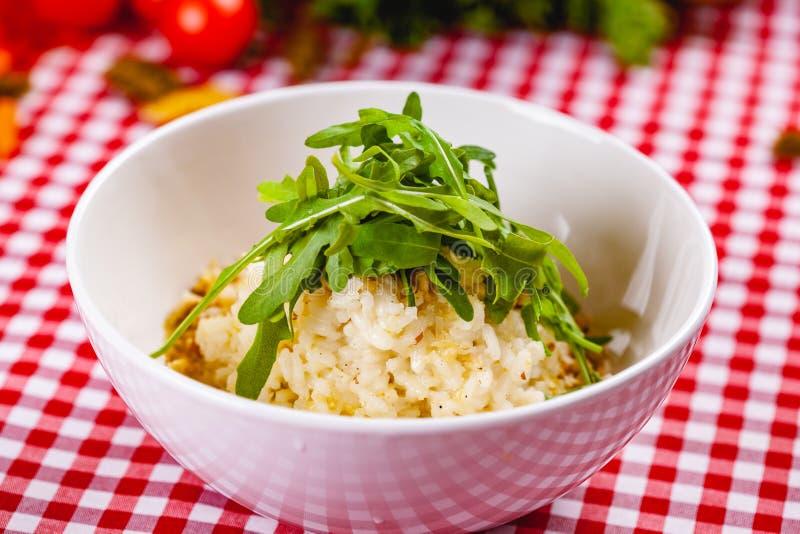 Risotto με gorgonzola, τα ξύλα καρυδιάς και το arugula στο άσπρο πιάτο στοκ φωτογραφία