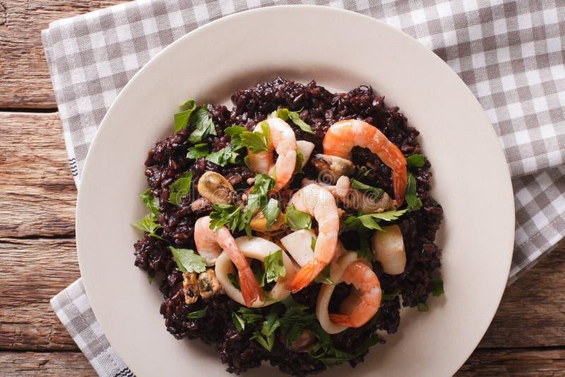 Risotto του μαύρου ρυζιού με στενό επάνω θαλασσινών σε ένα πιάτο horizont στοκ φωτογραφία