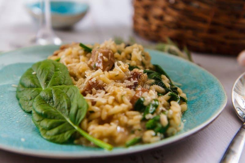 Risotto avec des champignons et des épinards d'un plat en céramique photo stock