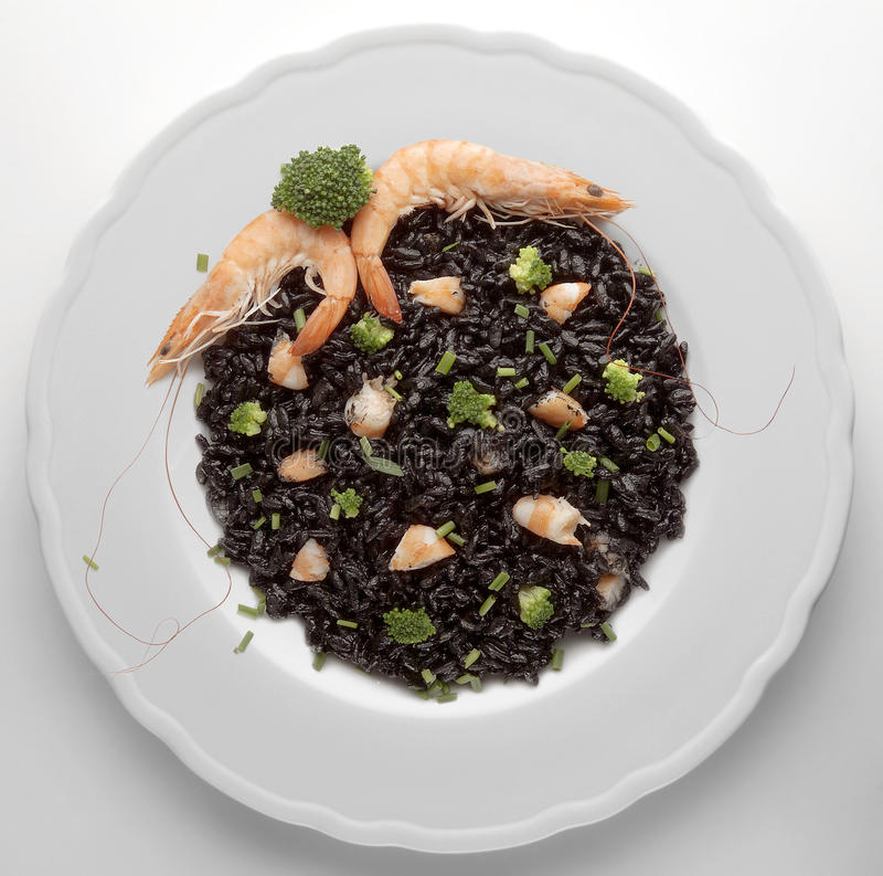 Risotto with black of cuttlefish and prawns stock image
