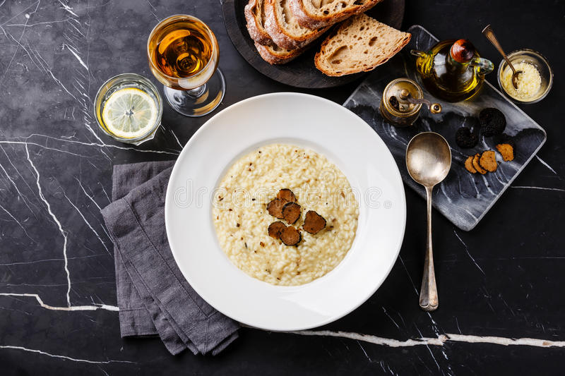 Risotto with black truffle. On plate on dark marble table background stock image