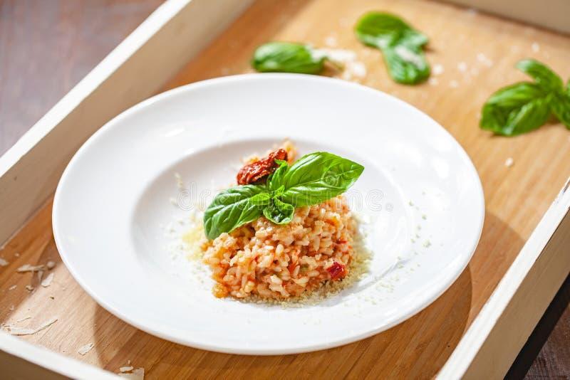 Risotto con i pomodori ed i capperi seccati al sole sul piatto bianco fotografia stock libera da diritti