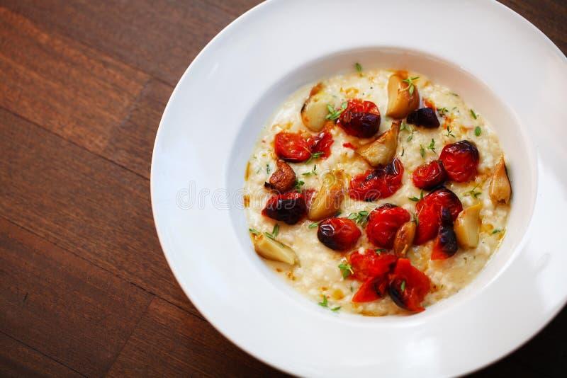 Risotto cremoso con los tomates y el ajo asados de cereza imágenes de archivo libres de regalías