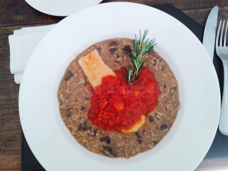 Risotto di Shitake con il brie e la salsa al pomodoro fotografia stock