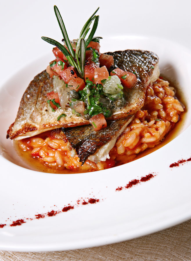 Risotto with fish. In white plate with vegetable royalty free stock photography