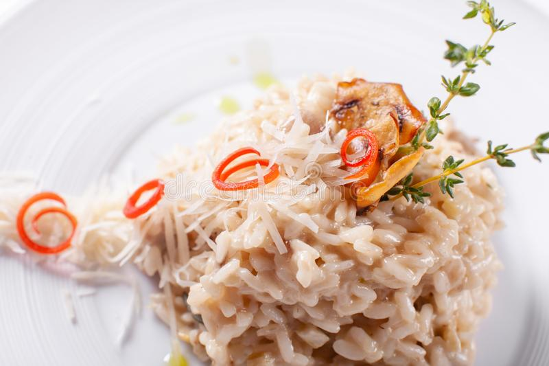 Risotto italien de plat avec les champignons et le parmesan blancs sauvages dans un plat blanc Menu méditerranéen de restaurant photo stock