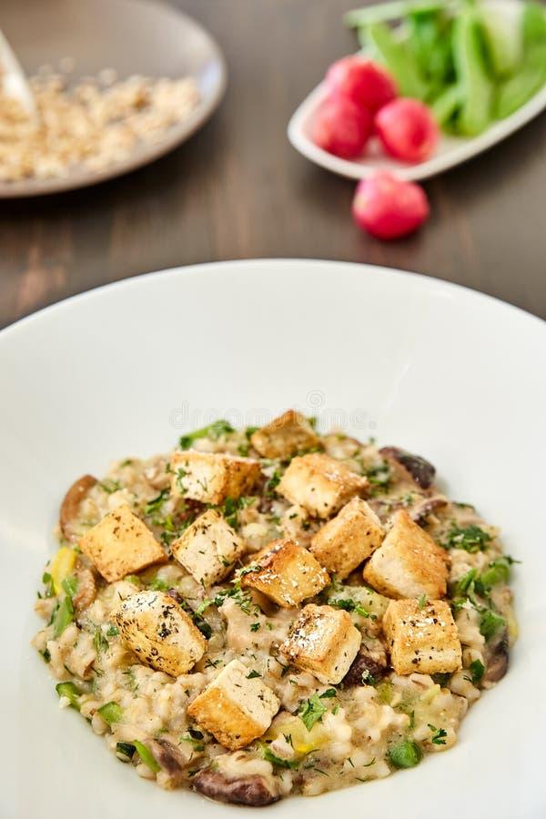 Risotto met paddestoelen, toost, parmezaanse kaas en greens in een grote witte plaat op een donkere houten lijst Op de achtergron stock fotografie