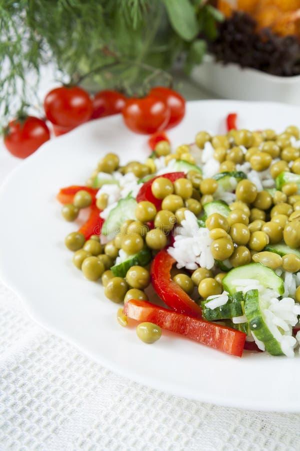 Risotto mit frischer Gurke, Rettichen, Pfeffer und grünen Erbsen stockbild