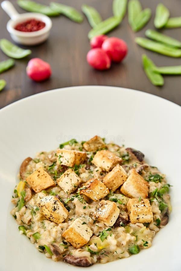 Risotto mit Pilzen, Toast, Parmesankäse und Grüns in einer großen weißen Platte auf einem dunklen Holztisch Im Hintergrund Rettic lizenzfreies stockbild