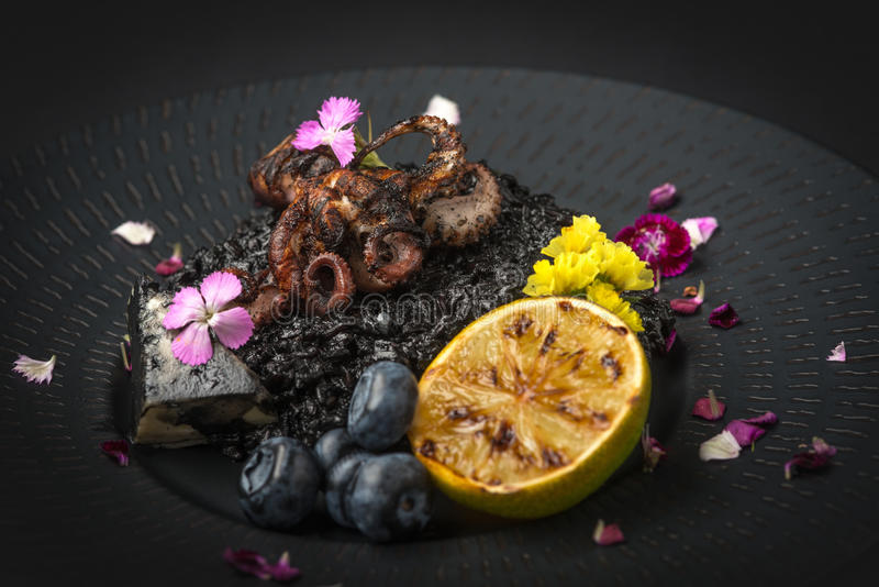 Risotto with octopus and blueberries on a black plate royalty free stock image