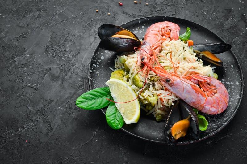 Risotto-Reis mit Gemüse und Meeresfrüchten Garnele und Miesmuscheln Auf dem alten Hintergrund stockbilder