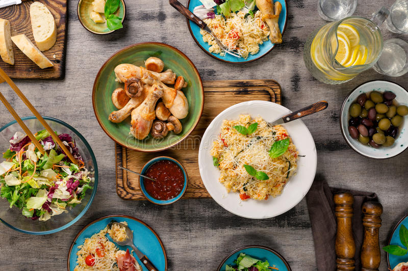 Risotto, roasted chicken legs, snacks and lemonade. Italian food. Risotto with cherry tomatoes, basil and parmesan cheese, roasted chicken legs, snacks and stock images