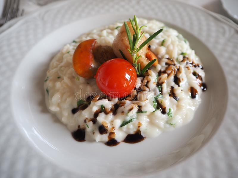 Risotto with seafood, cherry tomatoes and balsamic vinegar. Homemade Risotto with seafood, cherry tomatoes and balsamic vinegar royalty free stock photos