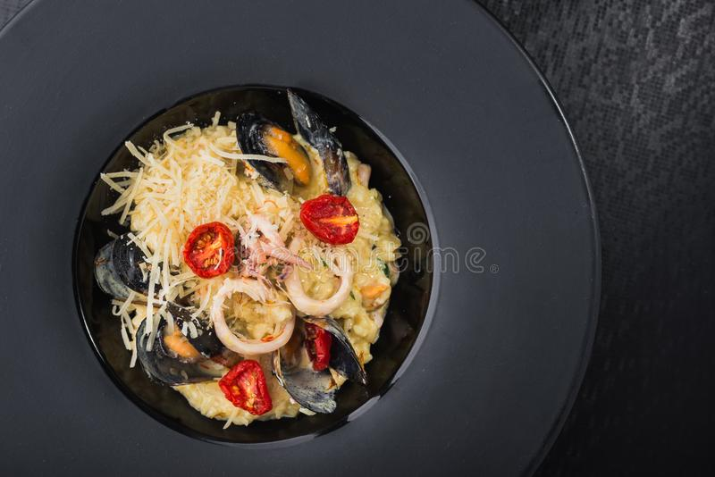 Risotto with seafood, mussel and squid. And italian cheese in black dish. restaurant serving meals royalty free stock photography