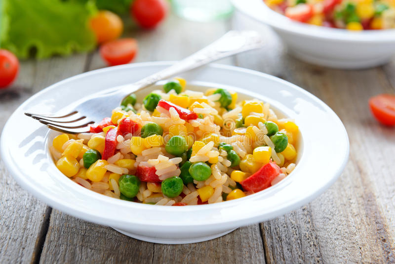 Risotto with vegetables in white plate on wooden table stock photo