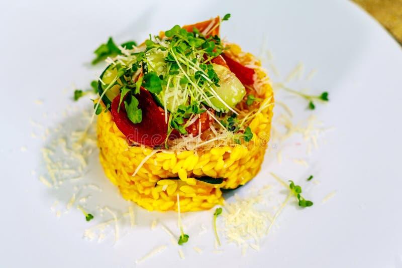 Risotto vegetariano con la zucca, lo zucchini, il parmigiano, la cipolla colorata con il succo della barbabietola ed i germi di s fotografie stock libere da diritti